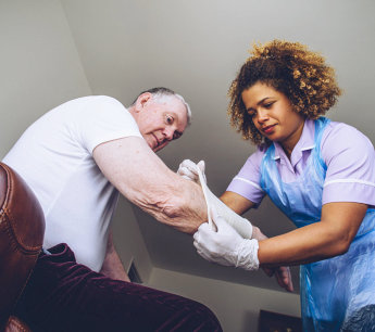 caregiver wrapping elderly man's arm